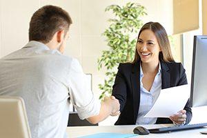 Jeune femme assise à un bureau qui donne la main à un homme pour conclure une entente