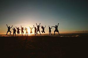 Groupe de gens qui sautent dans les airs sur la plage en signe d'esprit d'équipe