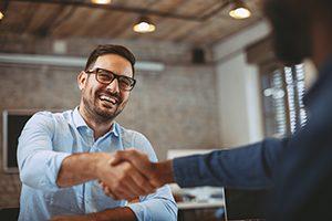 Deux hommes assis dans un café qui se donnent la main