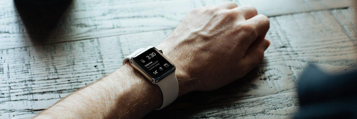 Bras d'un homme posé sur une table avec une montre intelligente
