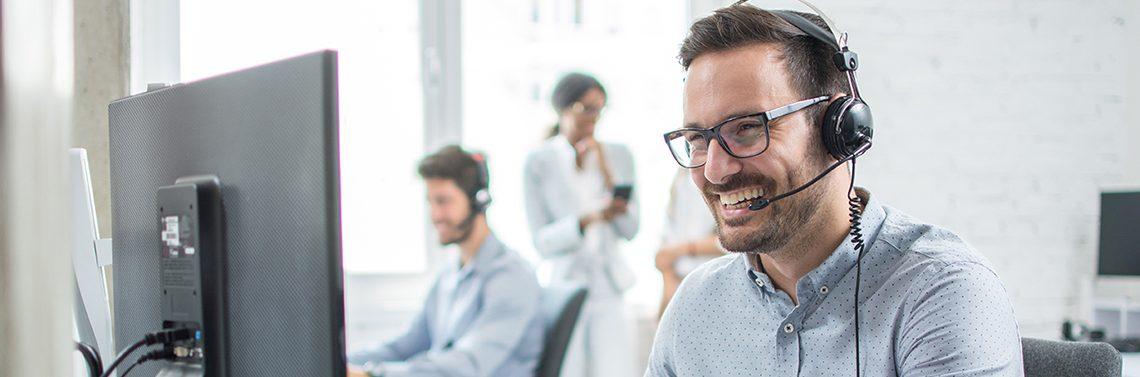 Homme souriant qui parle à un client dans un centre d'appels