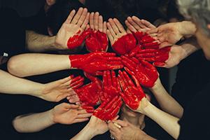 peinture rouge appliquée sur un groupe de mains pour former un coeur