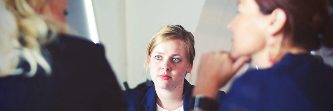 Jeune femme blonde en réunion avec deux autres femmes vues de dos