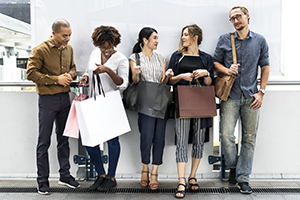 Groupe de gens debout contre un mur avec des sacs d'achat