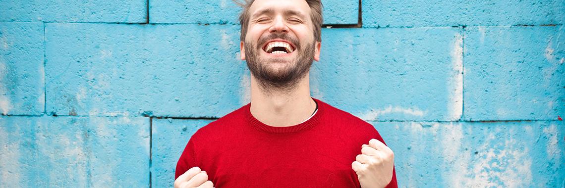 Homme au chandail rouge heureux devant un mur bleu
