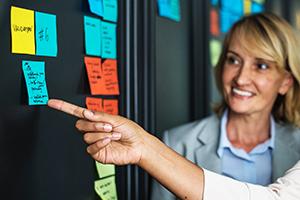 Femme d'affaires qui regarde une main qui pointe à un post-it sur un tableau
