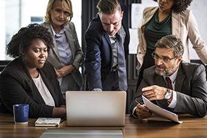 Cinq employés concentrés sur un écran d'ordinateur