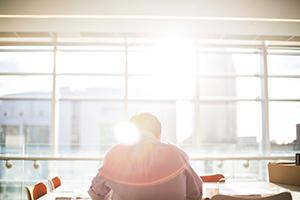 Homme travaillant devant une fenêtre avec le reflet du soleil