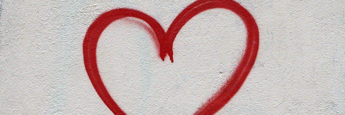 Coeur rouge dessiné sur un mur de béton blanc
