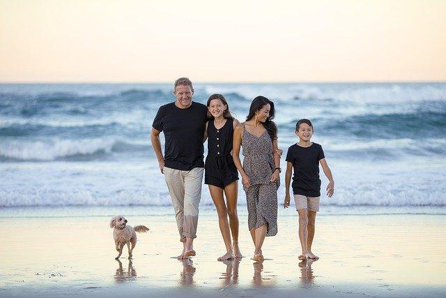 Famille de 4 avec chien devant la mer, les pieds sur le sable humide