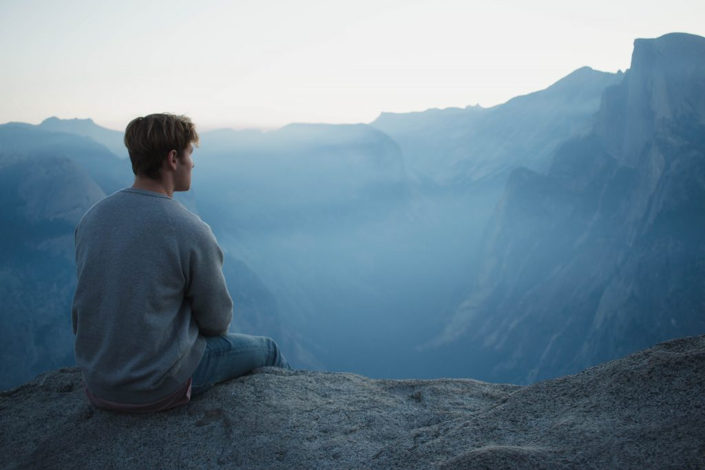 homme assis en contemplation devant paysage brumeux mais serein, médite en plein conscience