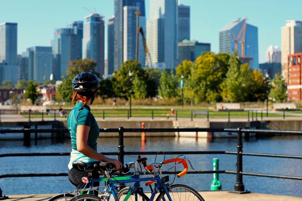 femme debout, la main sur la selle de son vélo accoté contemple la ville de Montréal. Les arbres sont verts et les bâtiments reflètent au soleil