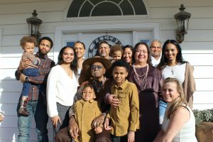 grande famille unie posant devant la porte principale de leur maison