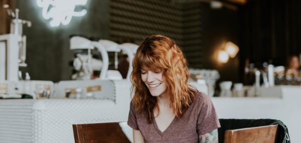 Jeune femme rousse souriante assise dans un café
