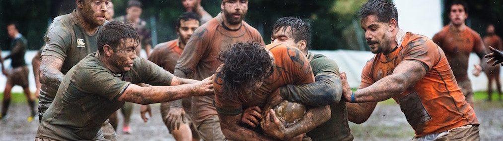 Groupe de joueurs de rugby masculin couverts de boue