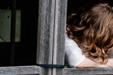 Femme dont on ne voit pas le visage les bras sur le bord d'une fenêtre