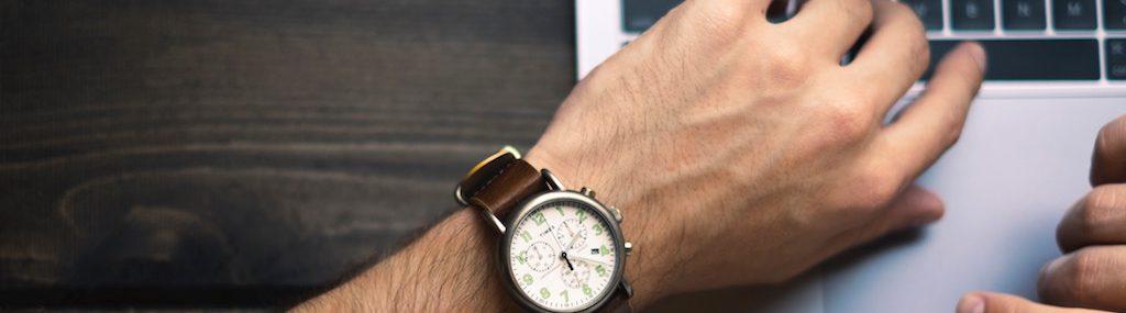 Homme qui travaille sur un portable et regarde sa montre analogue