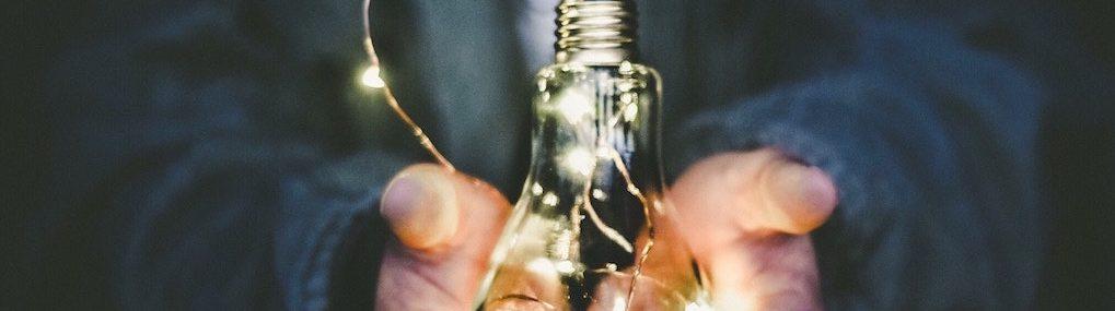 Ampoule illuminée dans les mains de quelqu'un