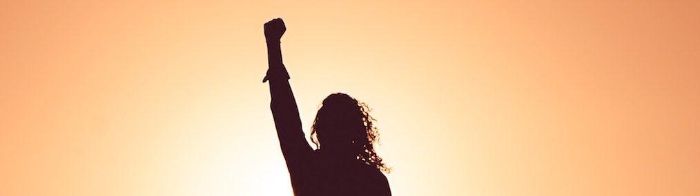 Profil de femme le poing en l'air en victoire