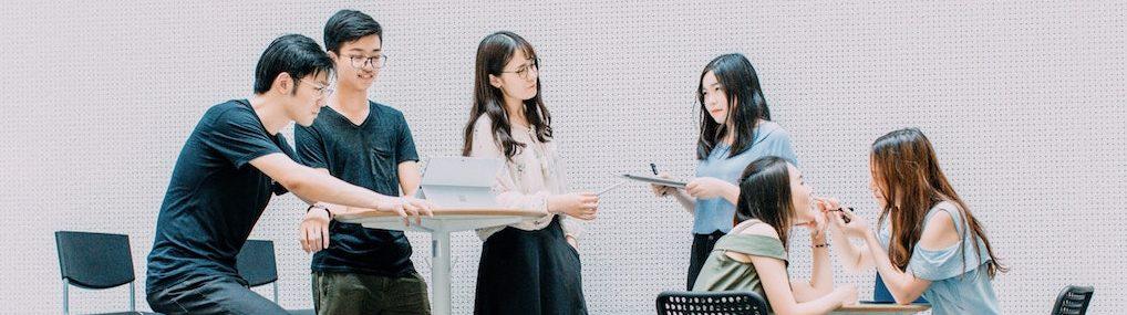 Groupe d'employés asiatiques qui discutent de leurs projets dans une aire commune