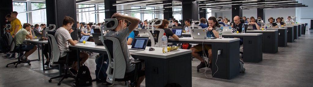 Centre de travail informatique où des centaines de gens travaillent en rangée