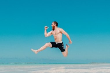Homme qui saute de joie sur la plage devant un ciel azur