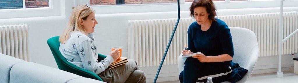 Deux femmes assises dans une aire de pause en réunion