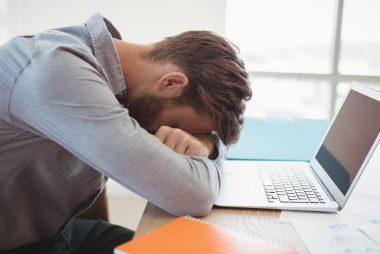 Gestionnaire épuisé la tête sur son ordinateur