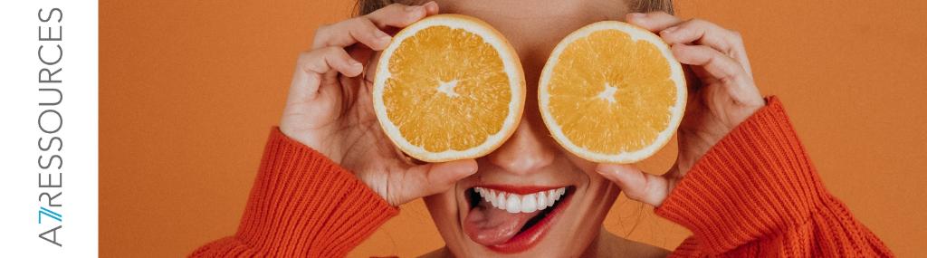 Femme qui tient des tranches d'orange devant ses yeux
