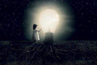 Fillette avec ampoule dans le noir