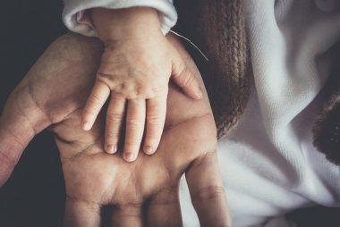 petite main de bébé posée sur main d'homme adulte paume à l'extérieur