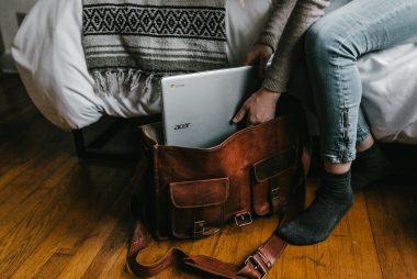 personne glisse laptop dans sac en cuir brun