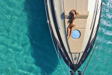 femme couchée en bikini sur le pont d'un yacht au milieu d'une eau turquoise
