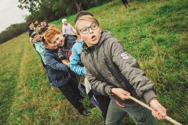 groupe d'enfants qui tirent sur une corde. jeu d'extérieur sur une pelouse