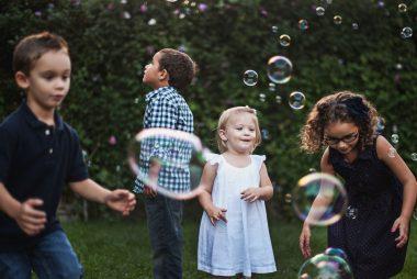4 enfants jouent avec de grosses bulles de savon